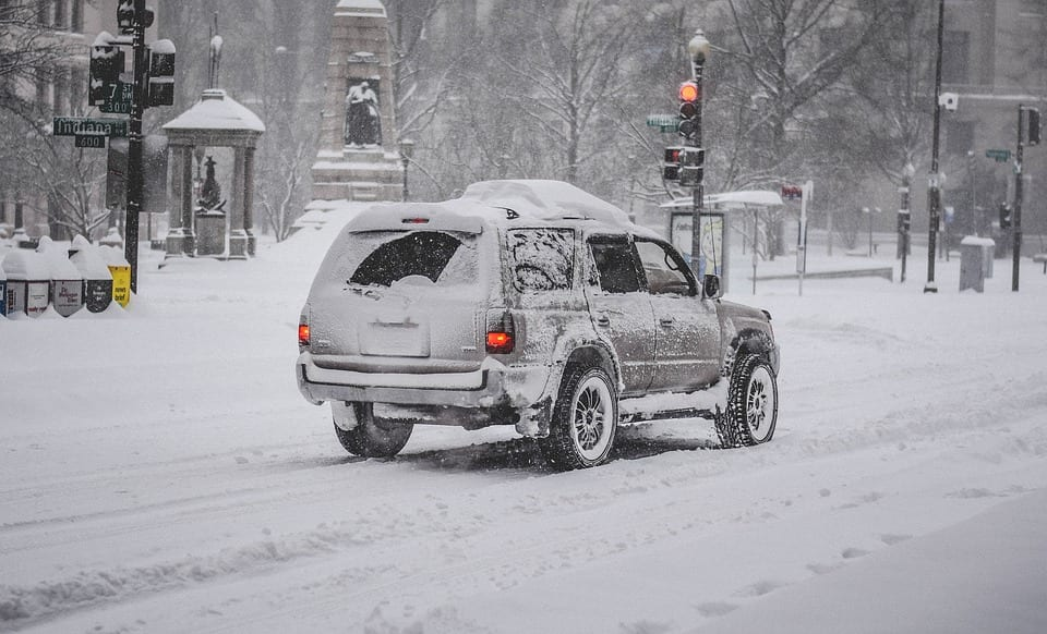 SUV driving down snowy road with snow tires