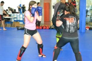 Women sparring in a kickboxing session - Kickboxing is an intense way to burn more calories