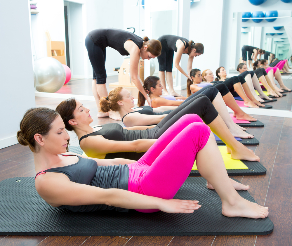 group of people doing pilates workout in gym
