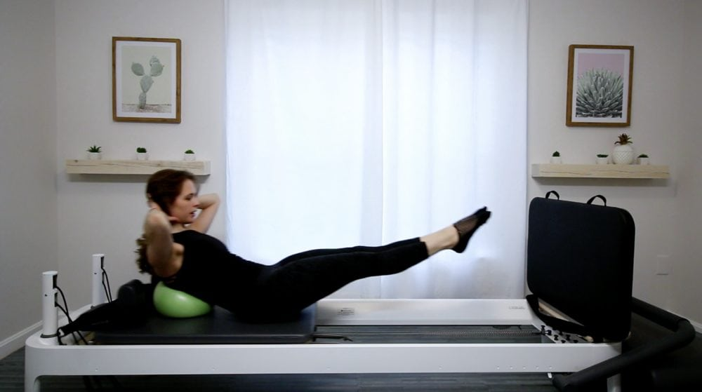 Pilates jumpboard woman doing situp variation on jumpboard