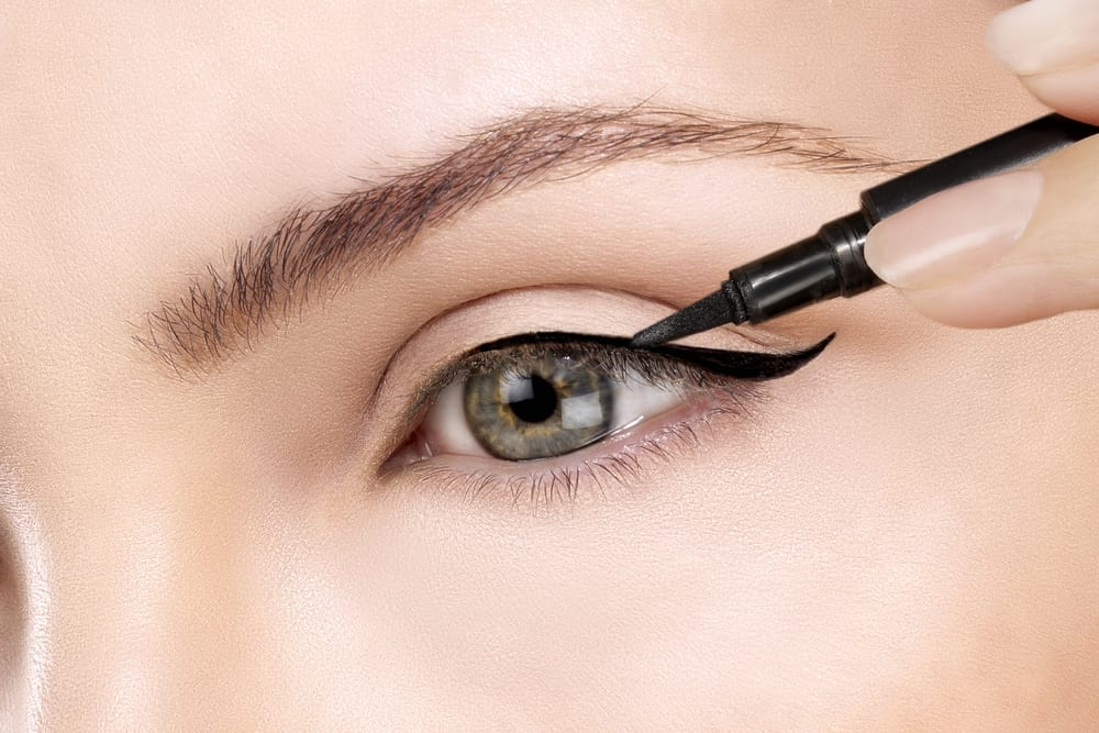 Beautiful model applying eyeliner closeup on eye for her makeup for winter