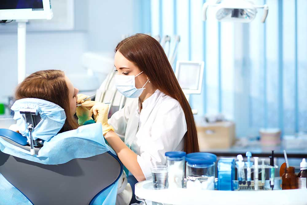 A dental hygienist working on a patient - the job is one of the best jobs doesn't require studying medicine in college