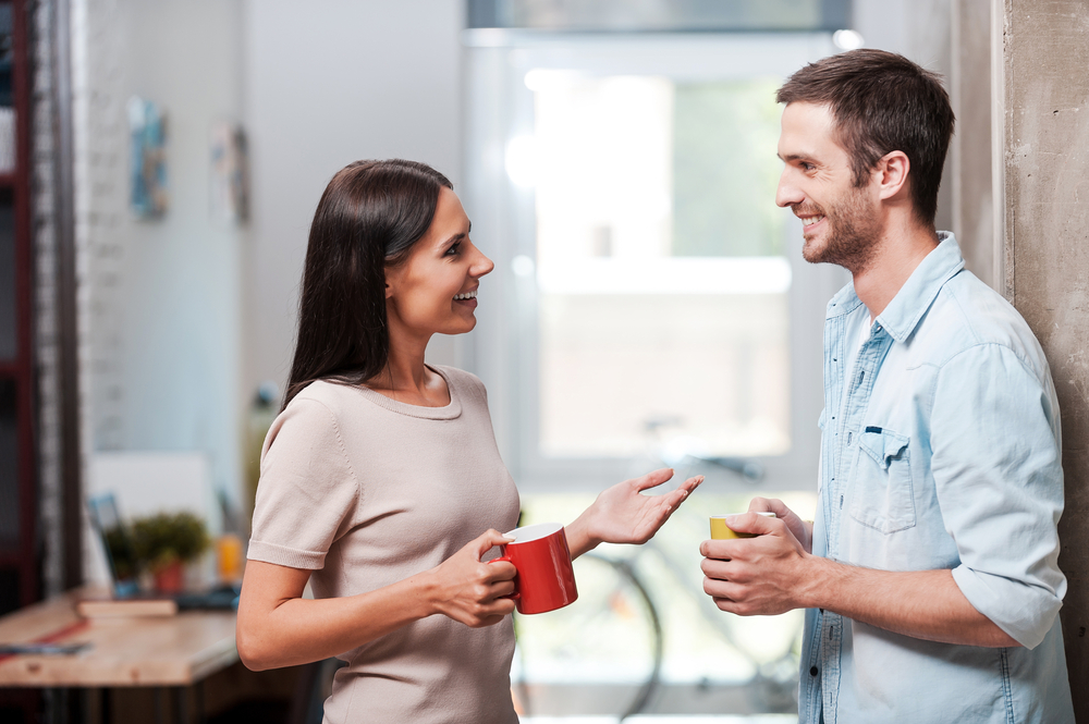 two people talking while drinking coffee