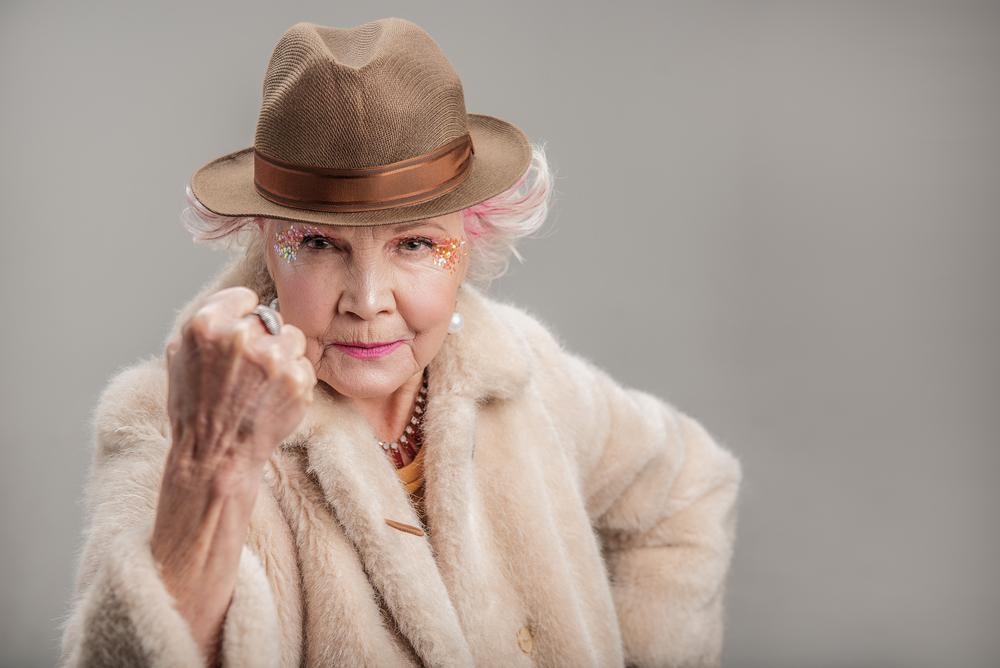 Grumpy senior lady in hat looking at camera