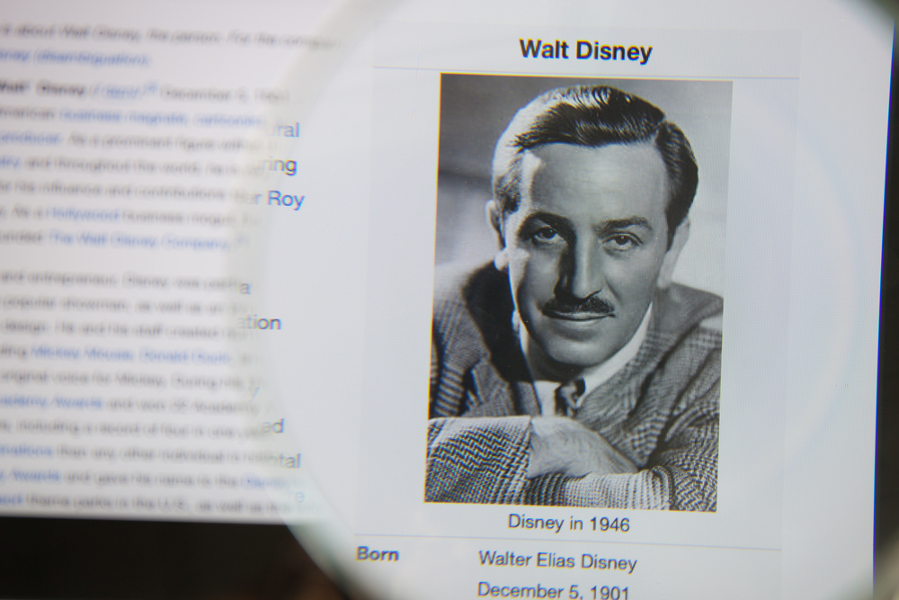 Photo of Wikipedia article page about Walt Disney on a ipad monitor screen through a magnifying glass.