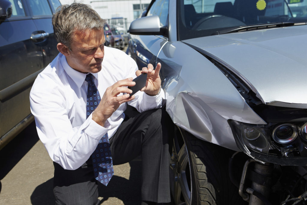 Fault adjuster checking out damage of a car - Ability to prove an accident was not your fault would help you reduce your auto-insurance rates