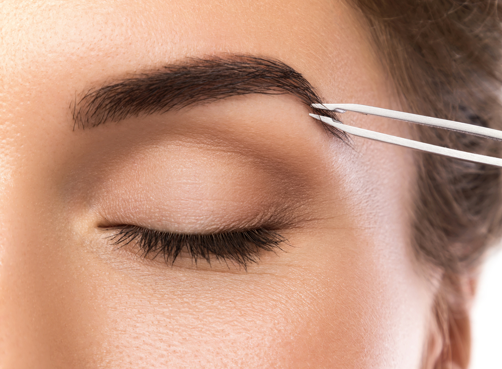 woman plucking her eyebrows with tweezers
