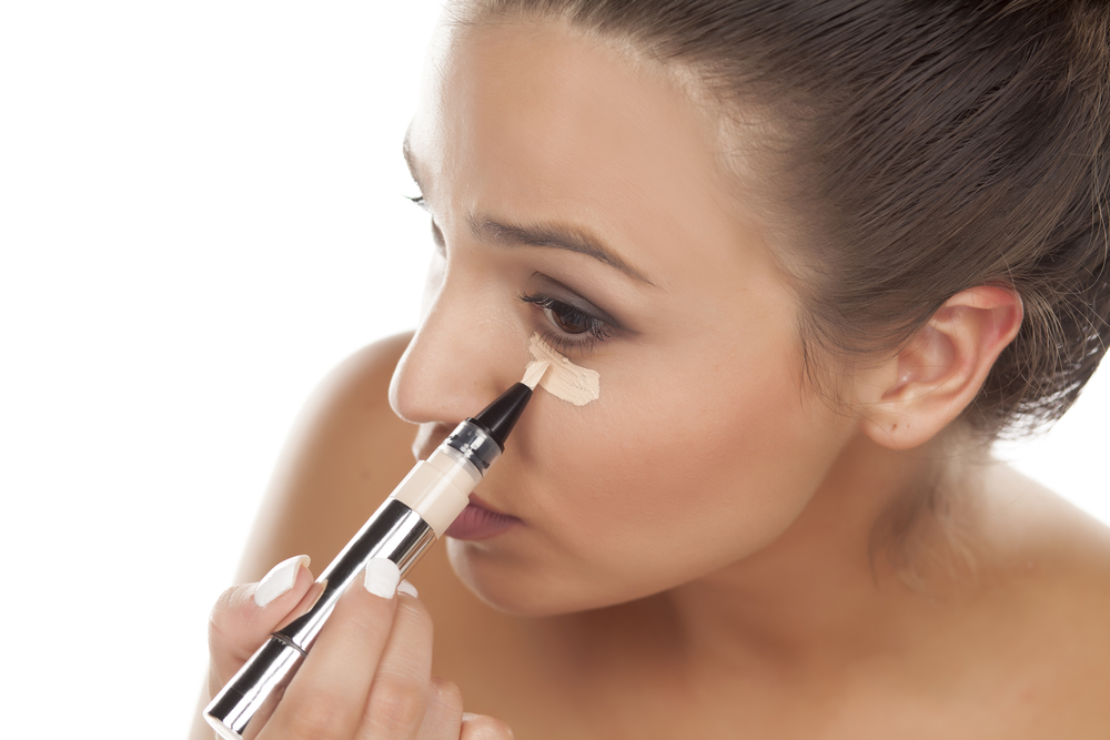 woman putting on concealer