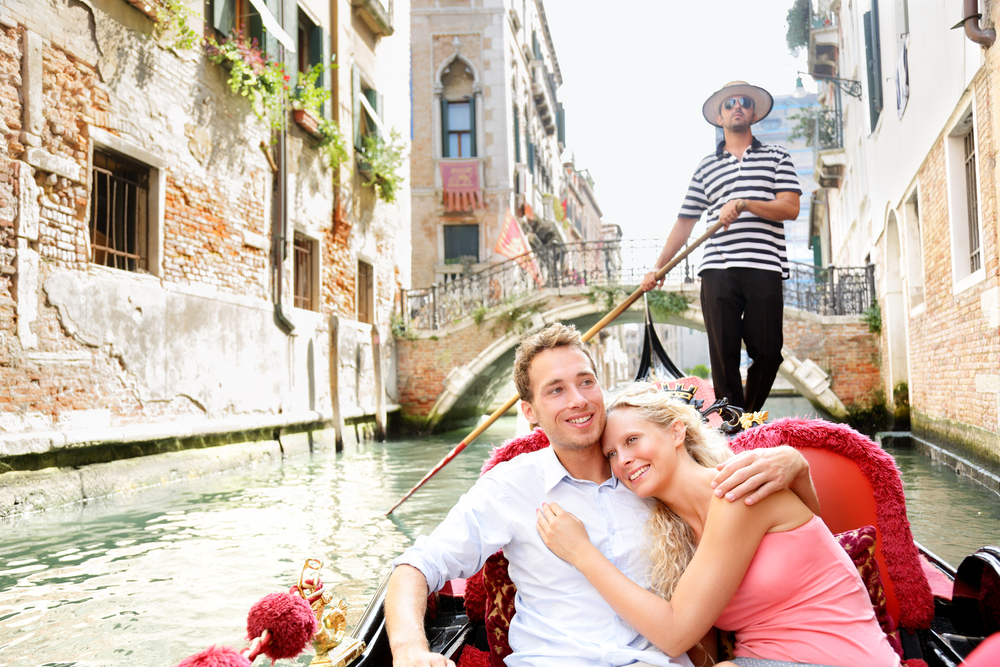 """Romantic couple traveling in Venice on a gondola ride = """"1000"""" height = """"667"""