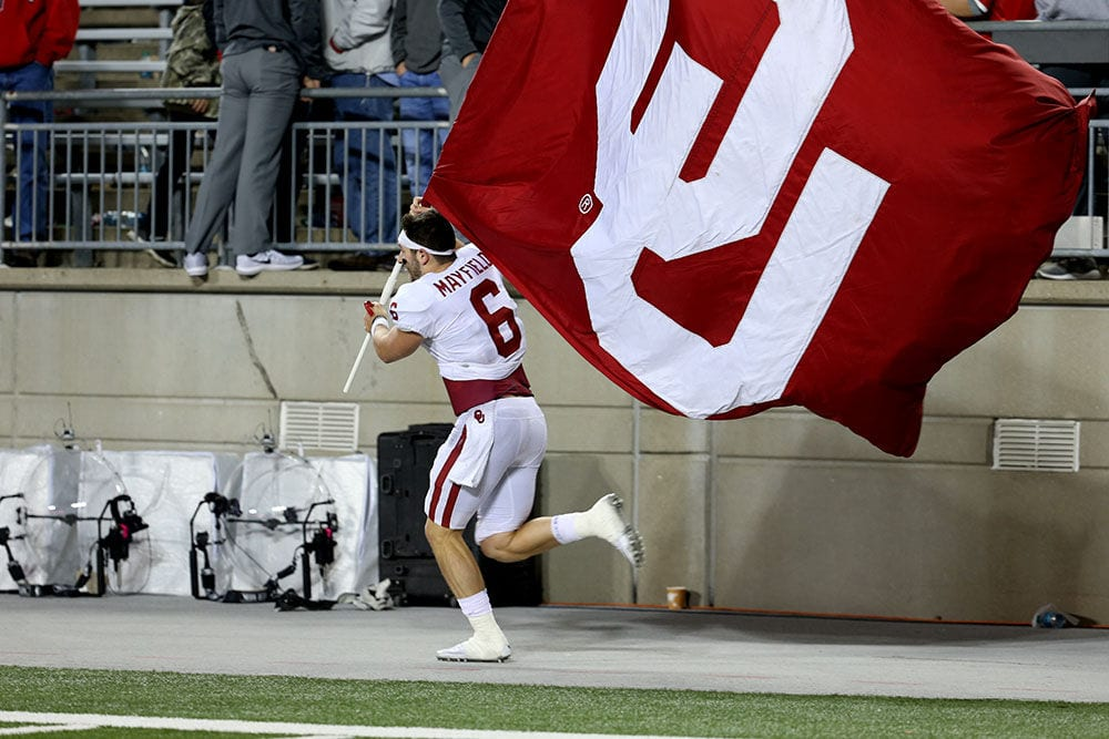 Football player running with college football flag
