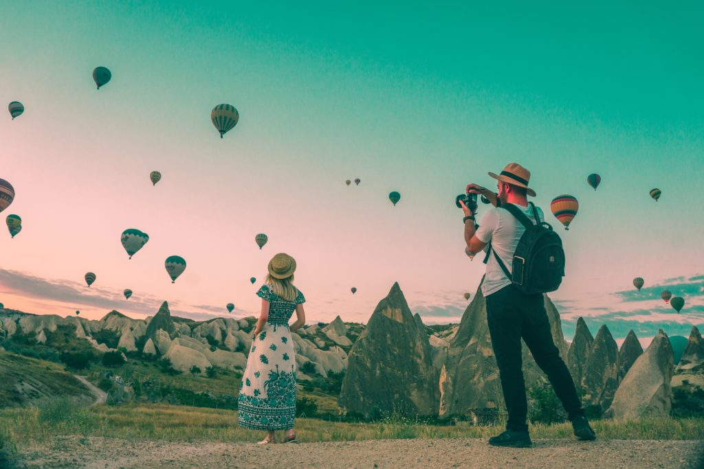 man taking photo of a woman with hot airballoons
