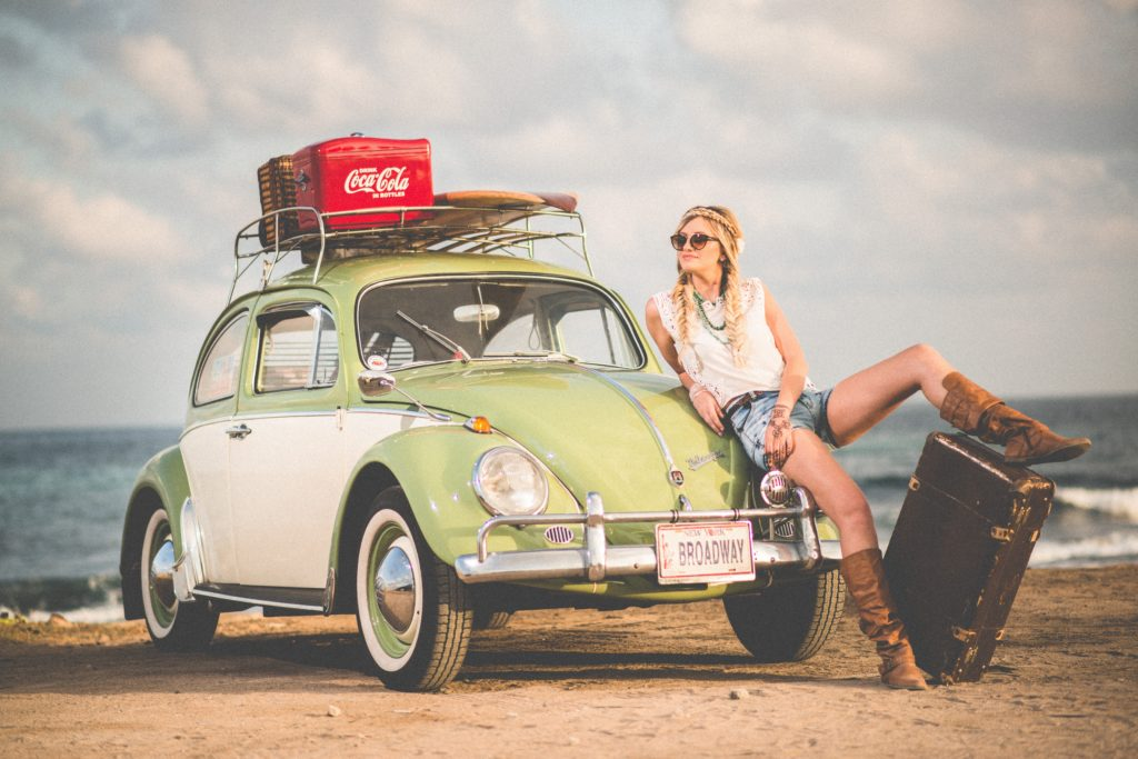 woman leaning on green and white volkswagen beetle