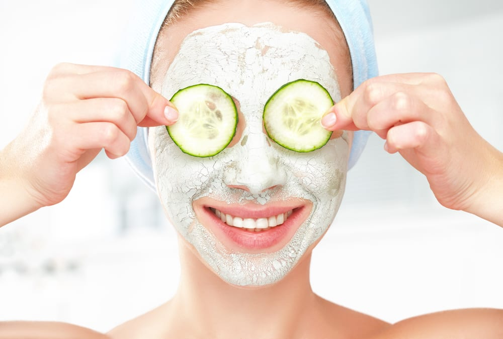 Woman with a face mask and cucumber on her eyes to reduce under-eye swelling