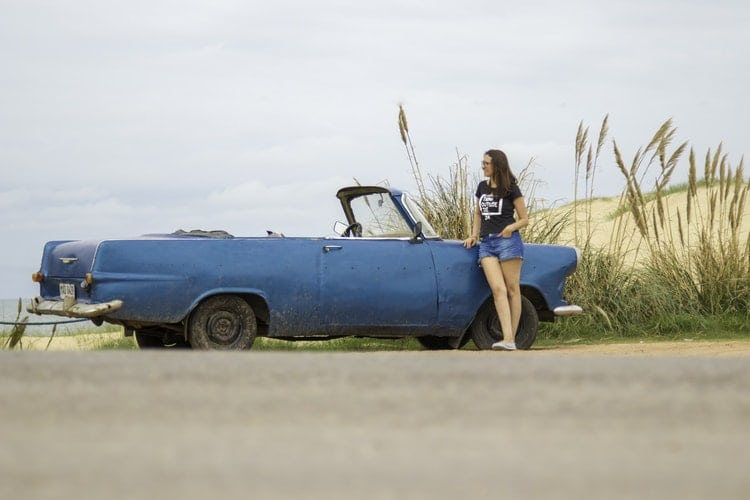 Girl next to blue car