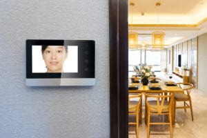 a wall monitor with video doorbell footage inside a home