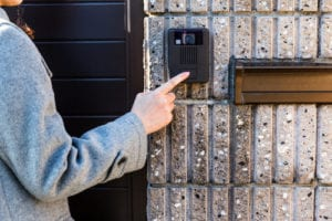 a woman ringing a video doorbell