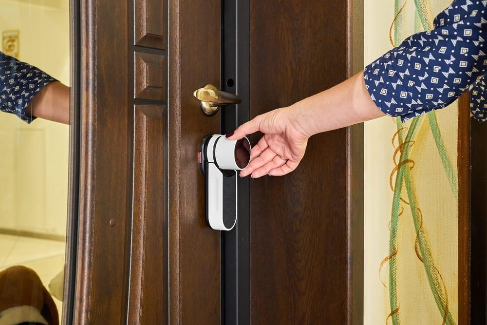 person using smart lock with smart home video doorbell
