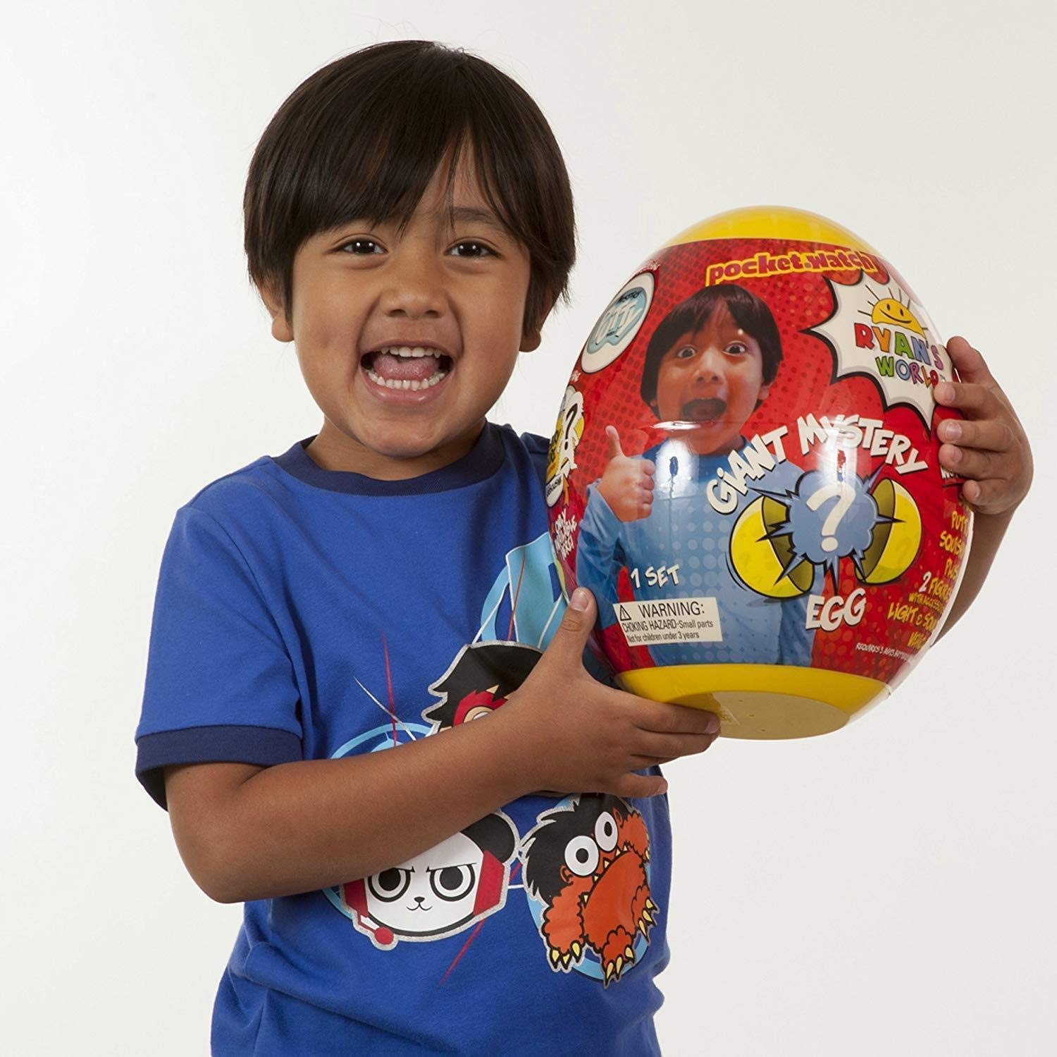 Ryan holding his Ryan World Surprise Egg holiday toys