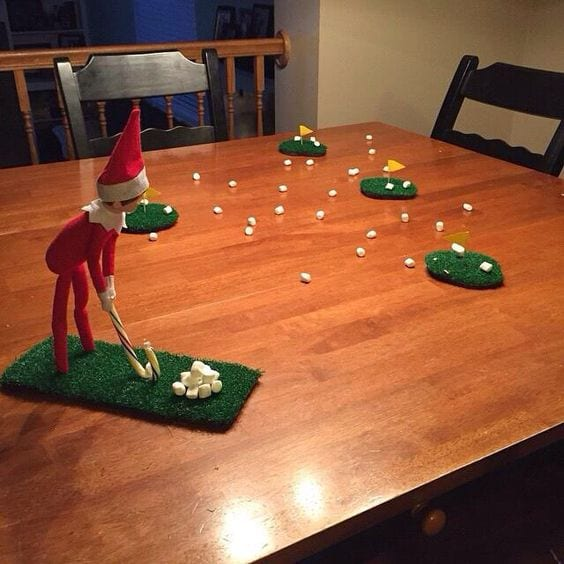 The elf is playing golf with marshmallows
