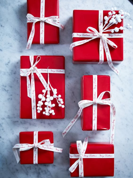 red christmas gift wrap with white ribbon and berries
