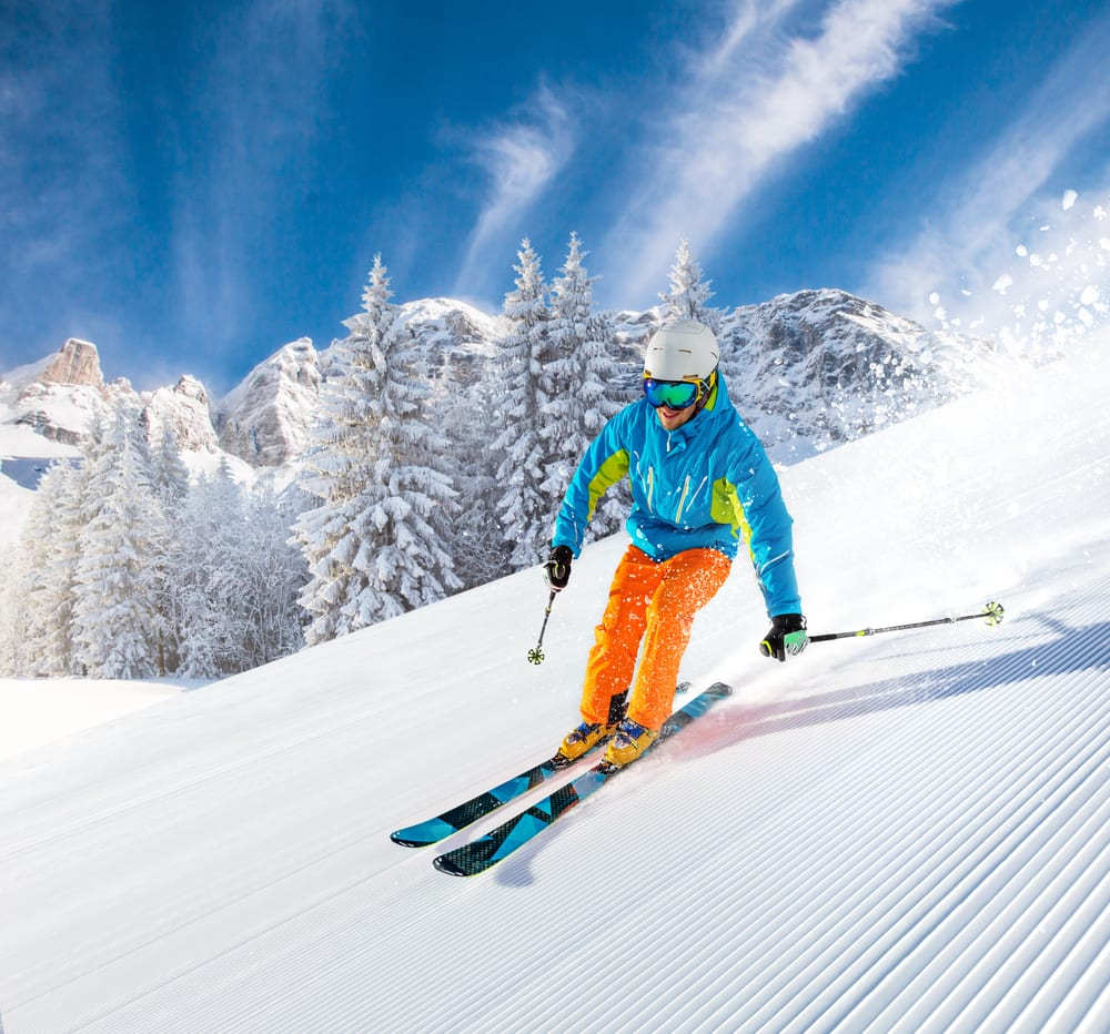 Skier skiing downhill in high mountains during their best winter vacation in USA