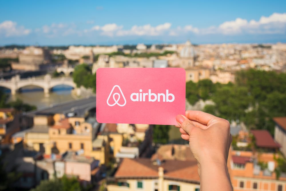 Person holding Airbnb logo in hand with city in background