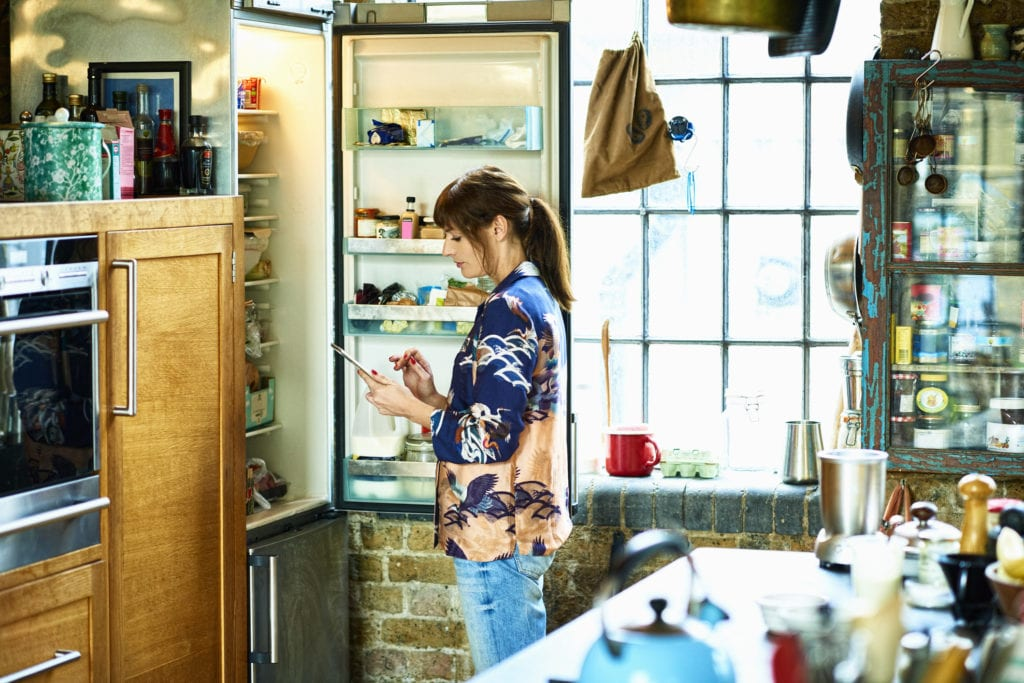woman looking in refrigerator