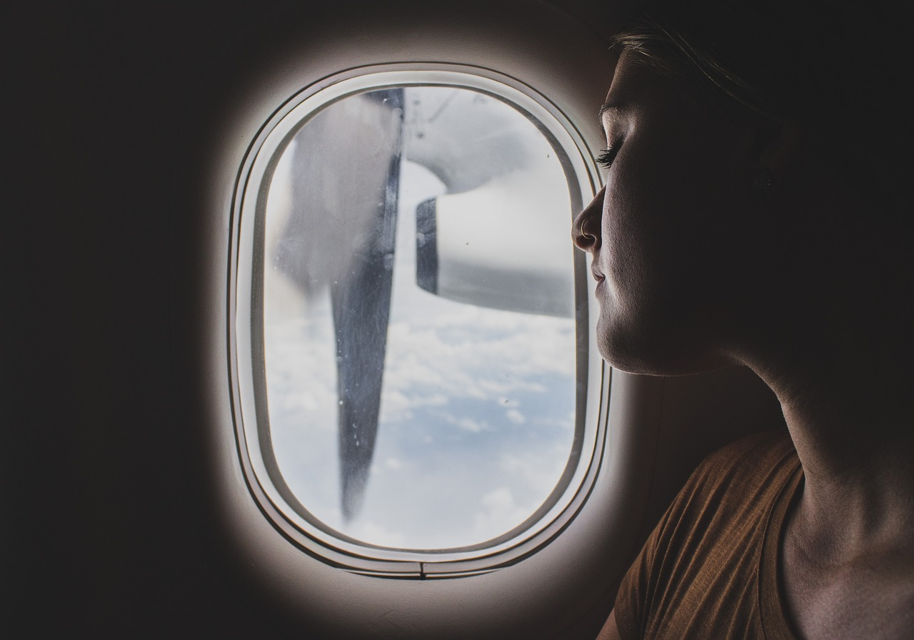 woman looking out of the window during her long haul flight