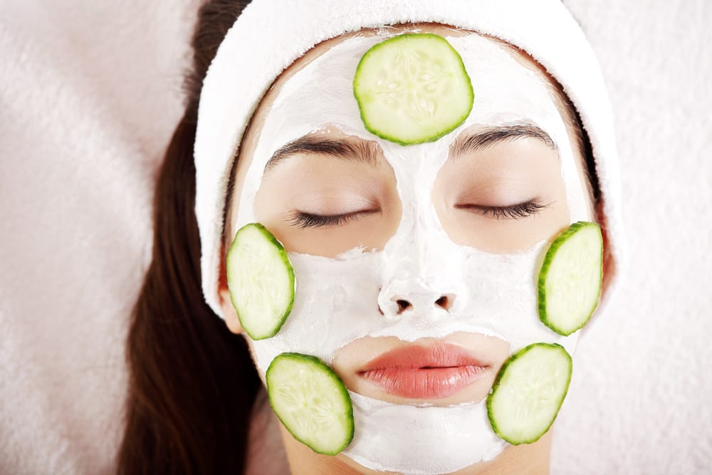Woman with cucumber slices on the face looking after her skin