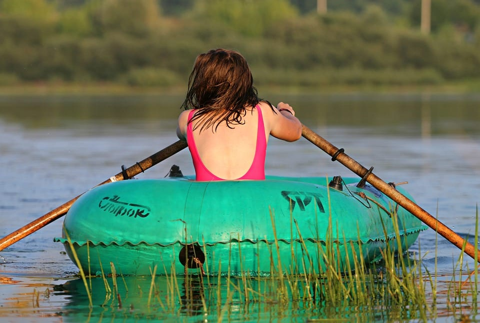 woman rowing inflatable boat in lake