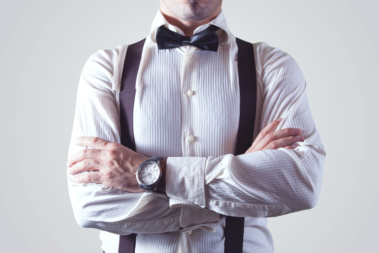 man wearing a bow tie with his arms crossed