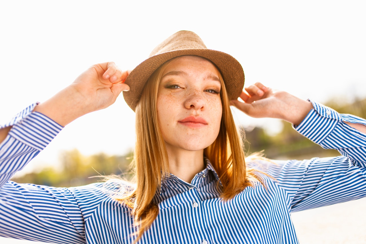 woman in a hat tilting her head towards the camera