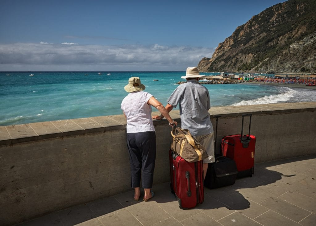 Two people looking out to the ocean with their bags
