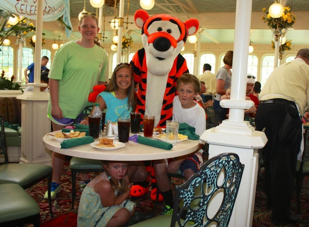 child hiding under a table on vacation as shes scared of tigger