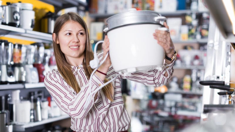 Happy woman choosing slow cooker in household appliances shop