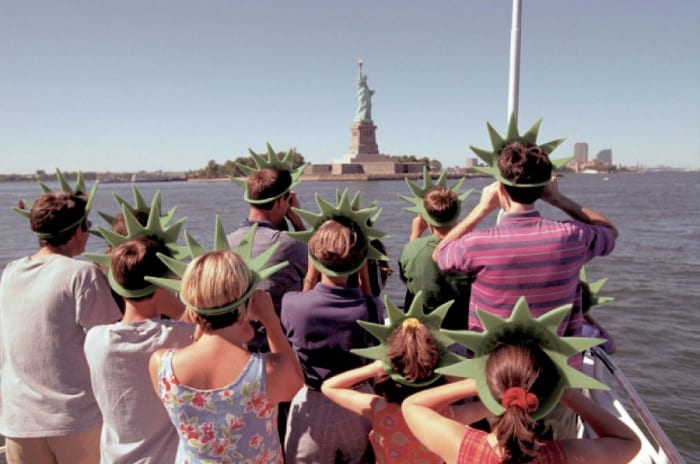 tourists on a boat going to see the statue of liberty wearing matching hats