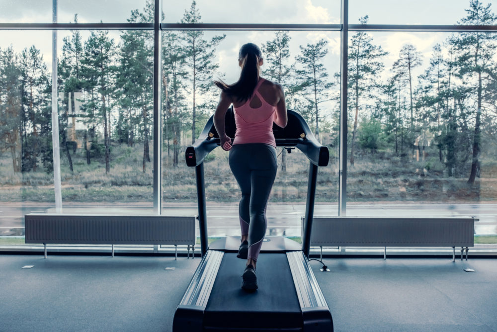 woman running on treadmill in front of window