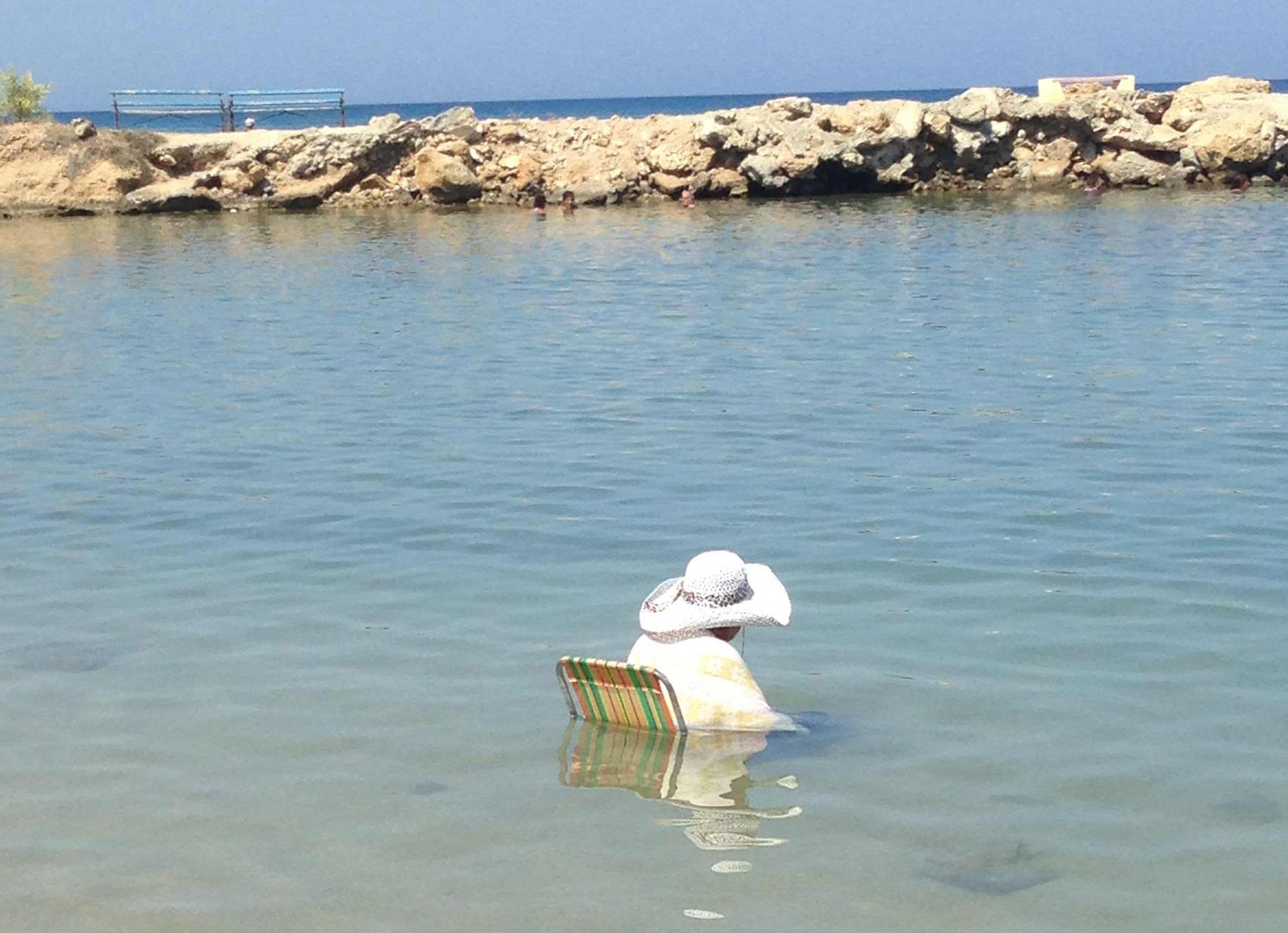 woman sitting in a deck chair in the sea