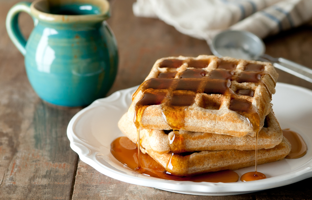 waffles with syrup on wooden table