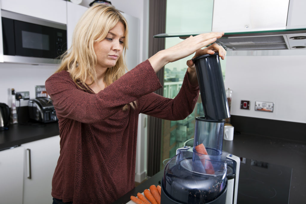 woman juicing carrots with best juicer