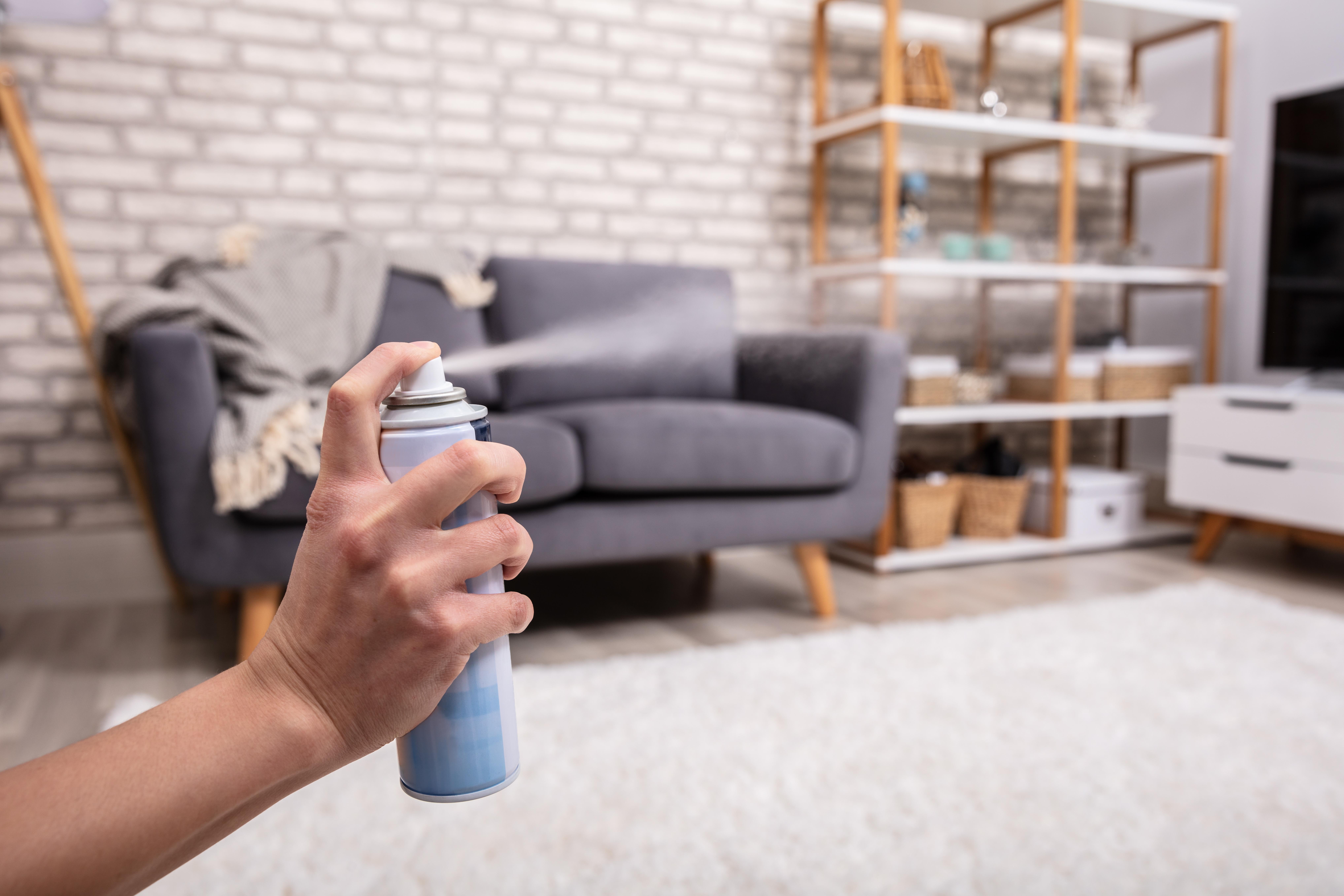 man spraying air freshener