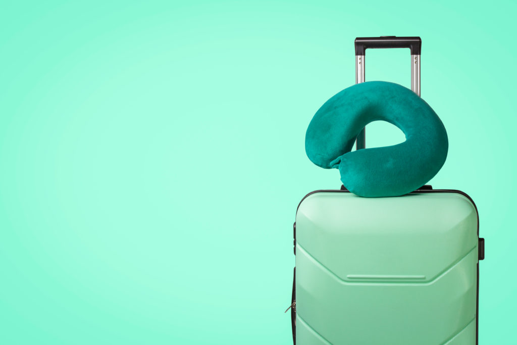 a green suitcase and travel pillow