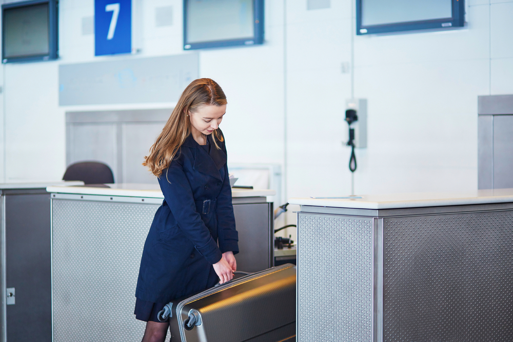 woman weighing luggage at the airport