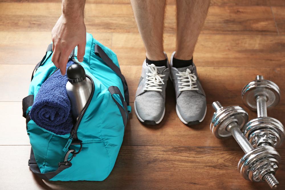 man reaching into gym bag
