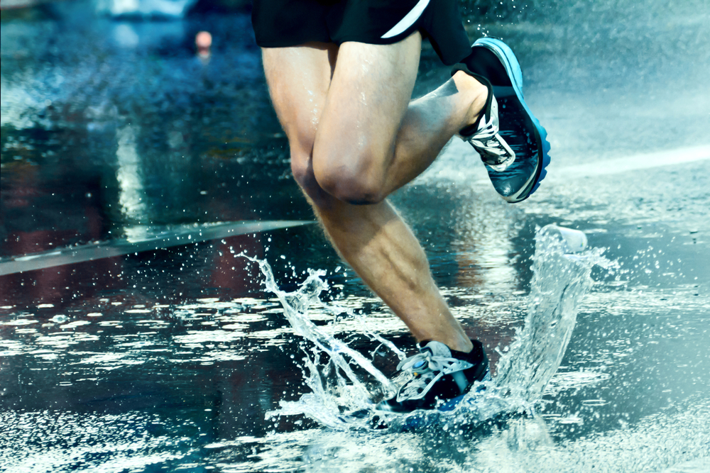 man running through a puddle