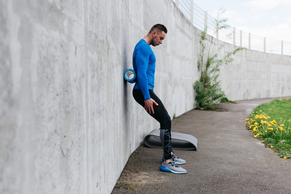 man using foam roller against a wall