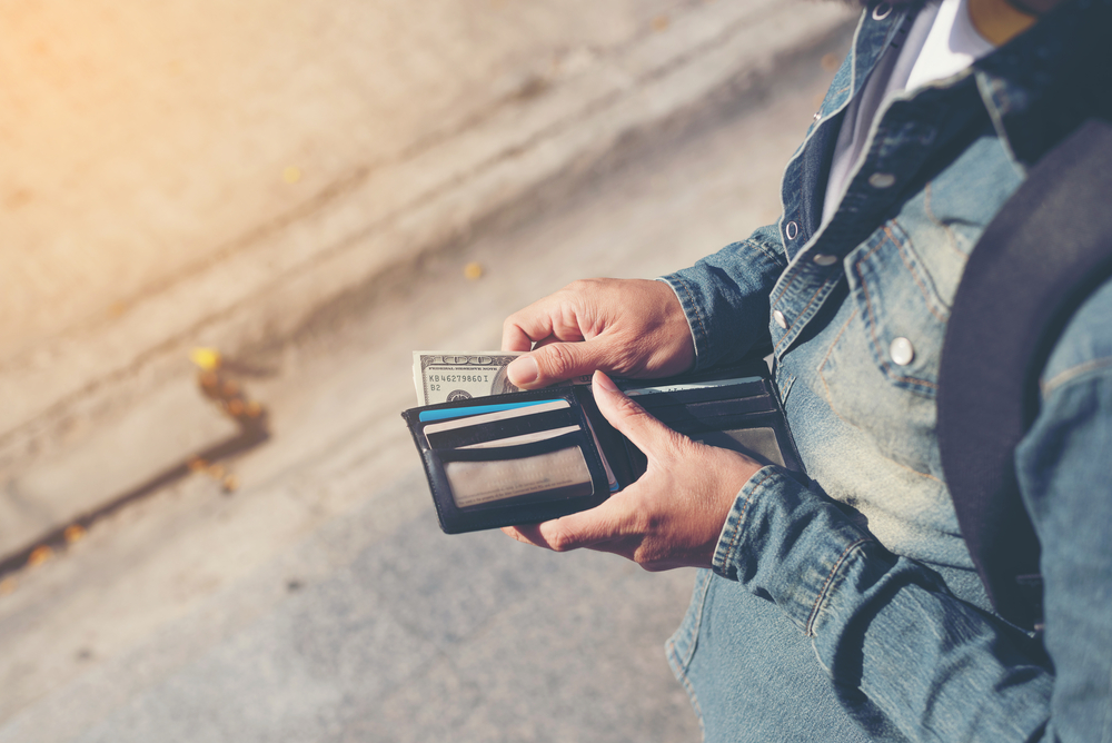 person holding wallets and cards