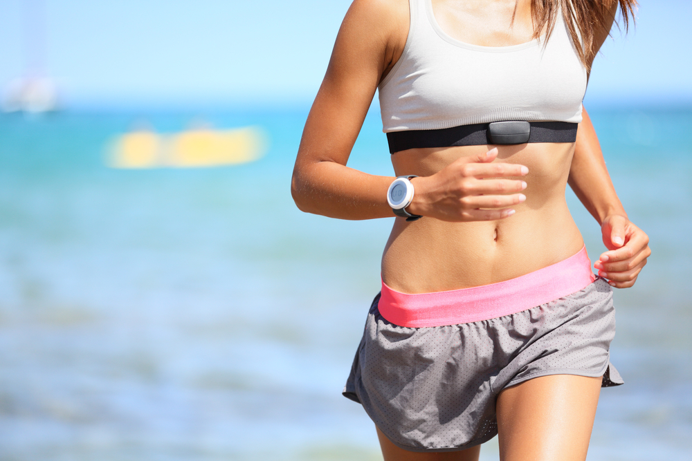 woman running and wearing a heart rate monitor