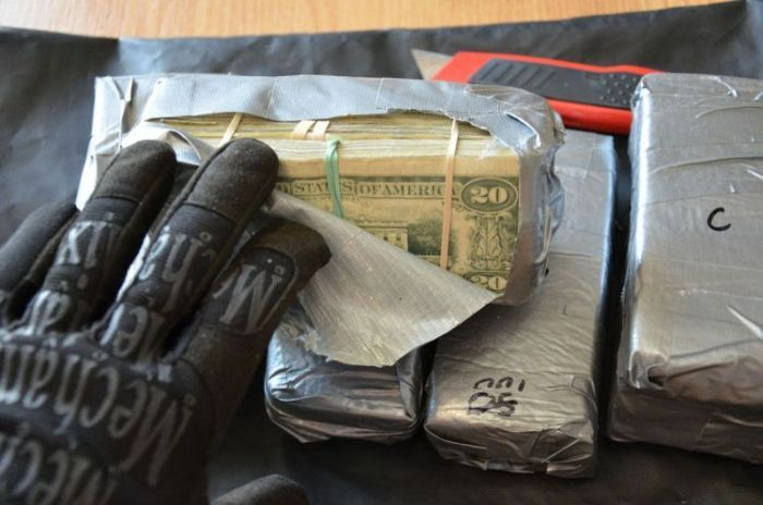 bills of money taped inside car in packages