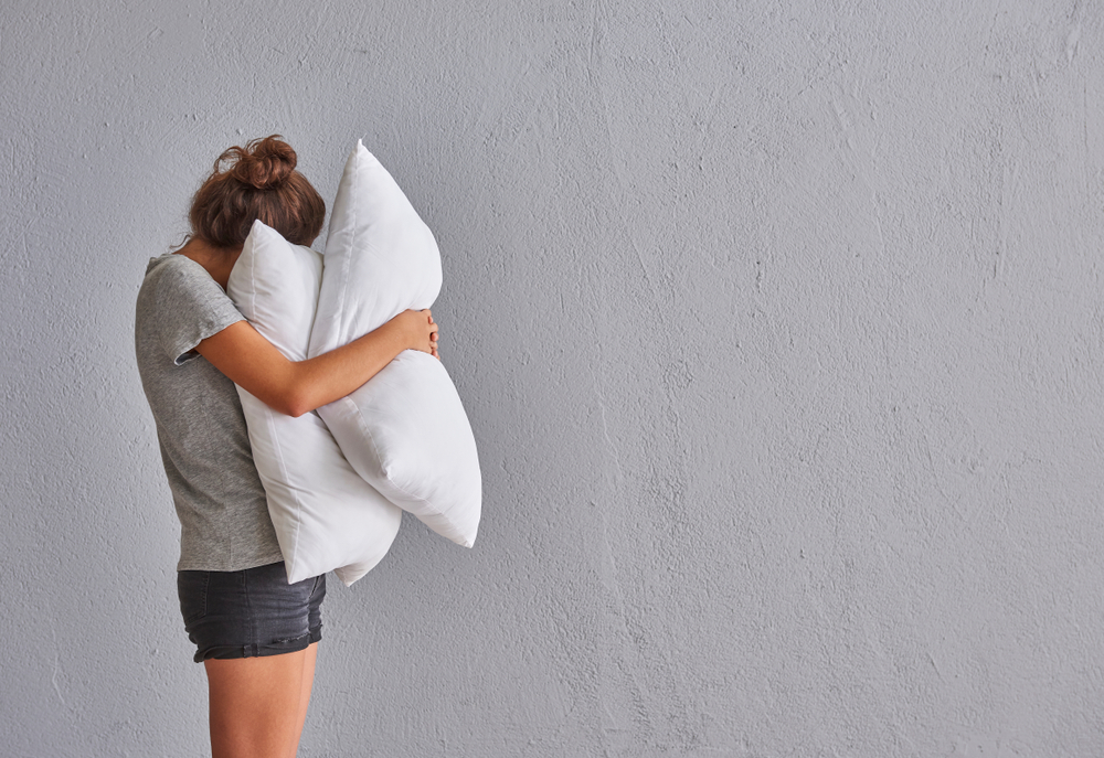 woman hugging pillows